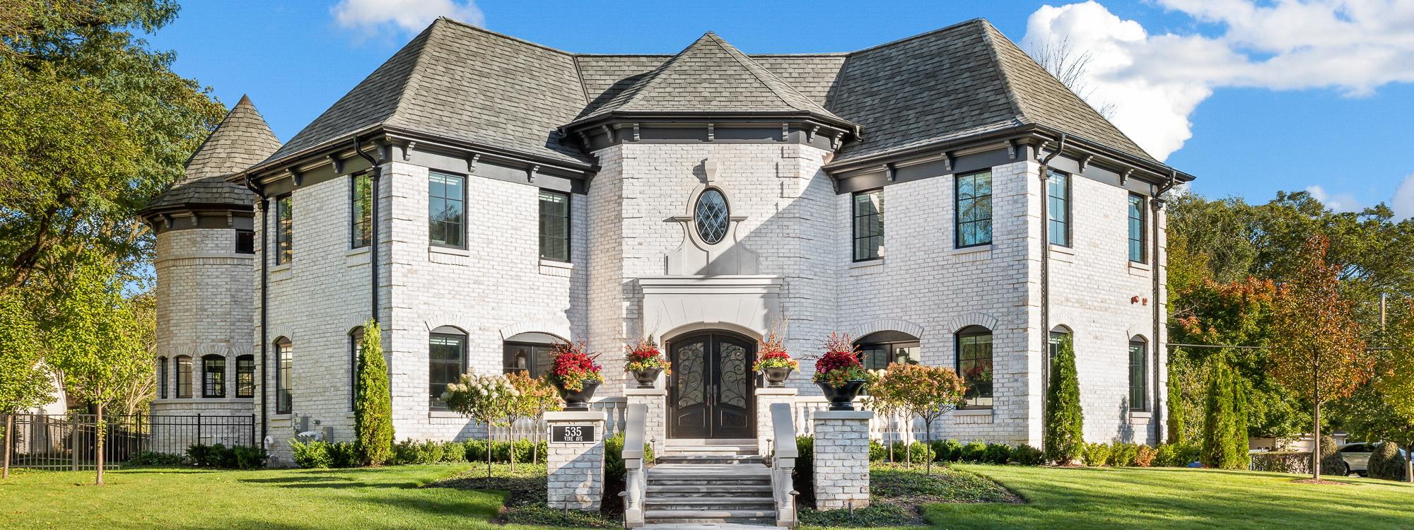Front of white brick, two-story luxury custom home with hip roof, double door entry, terrace and tourelle