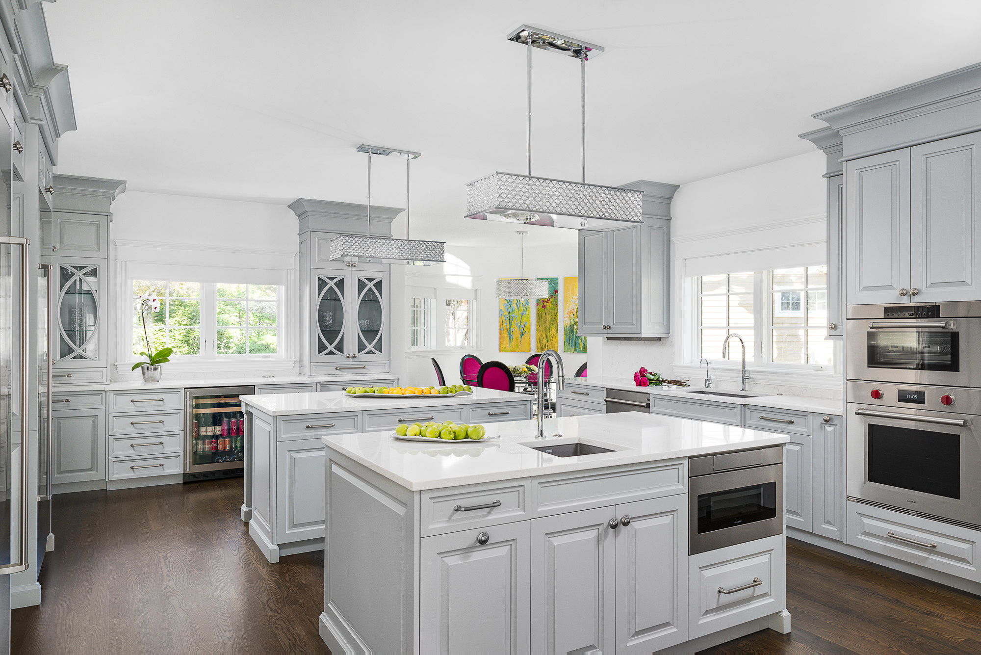 Luxury kitchen with dual islands, vegetable prep sink, white European cabinetry, custom mullion doors, M series wall oven, steamer, and microwave.